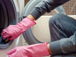 Picture of female hands in pink rubber glove washing washing mac